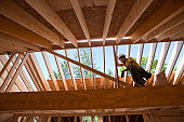 Hispanic carpenter with a circular saw on rafter at a house under construction