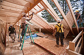 Hispanic carpenters installing roof panel through upper floor at a house under construction