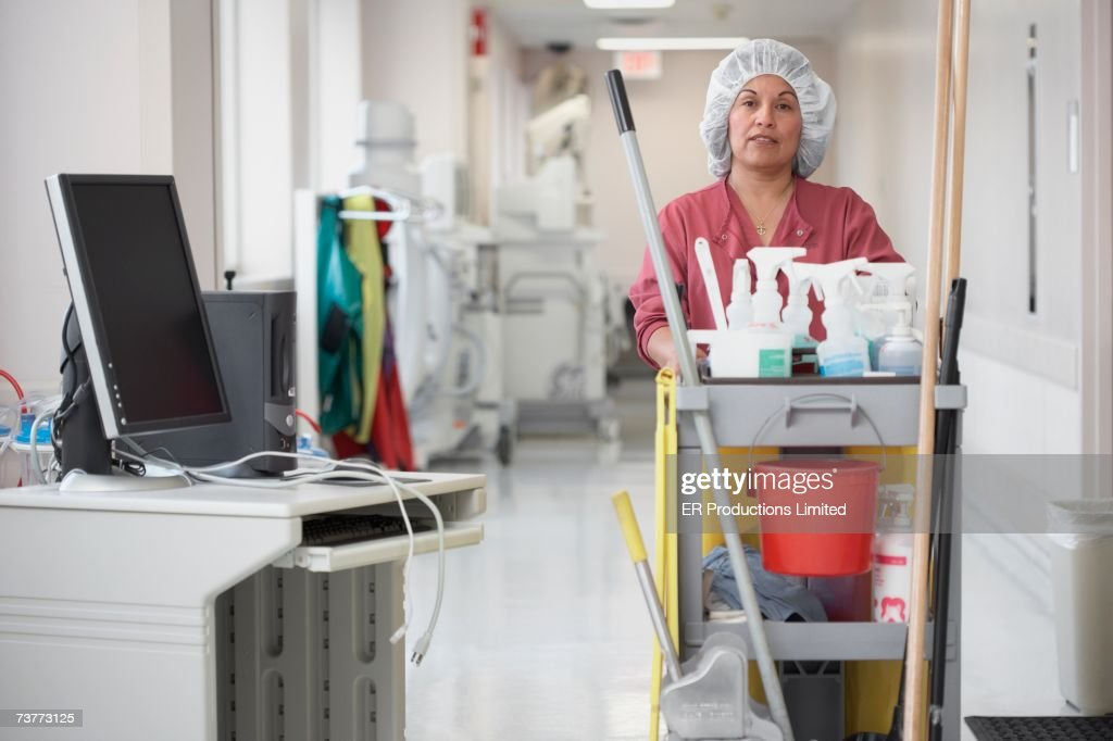 Hispanic cleaning woman pushing cart in hospital corridor