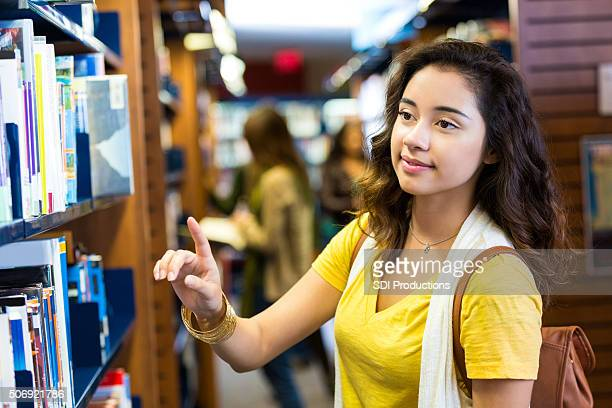 Hispanic college age girl searching for book in public library