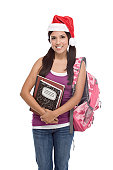 Christmas friendly Latina High school student schoolgirl wearing red Santa Claus hat with backpack