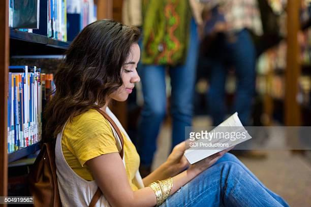 Hispanique collège étudiant assis dans la bibliothèque de livres de lecture