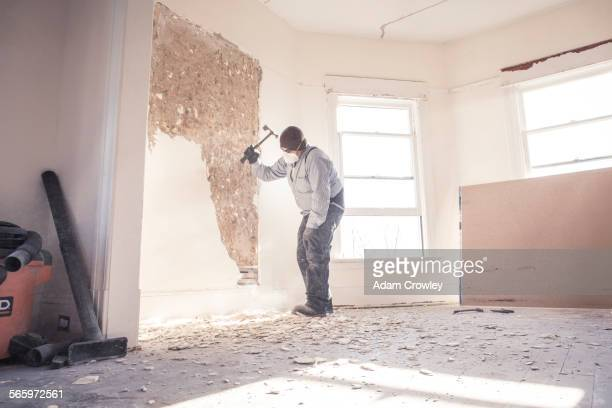 Hispanic construction worker demolishing wall