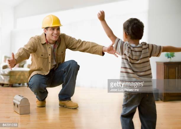 Hispanic construction worker greeting son