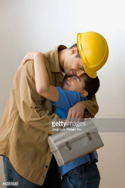Hispanic construction worker hugging son