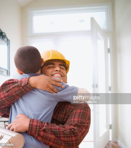 Hispanic construction worker returning home and hugging son