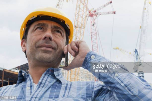 Hispanic construction worker talking on cell phone