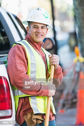 Hispanic construction worker with pickup and shovel