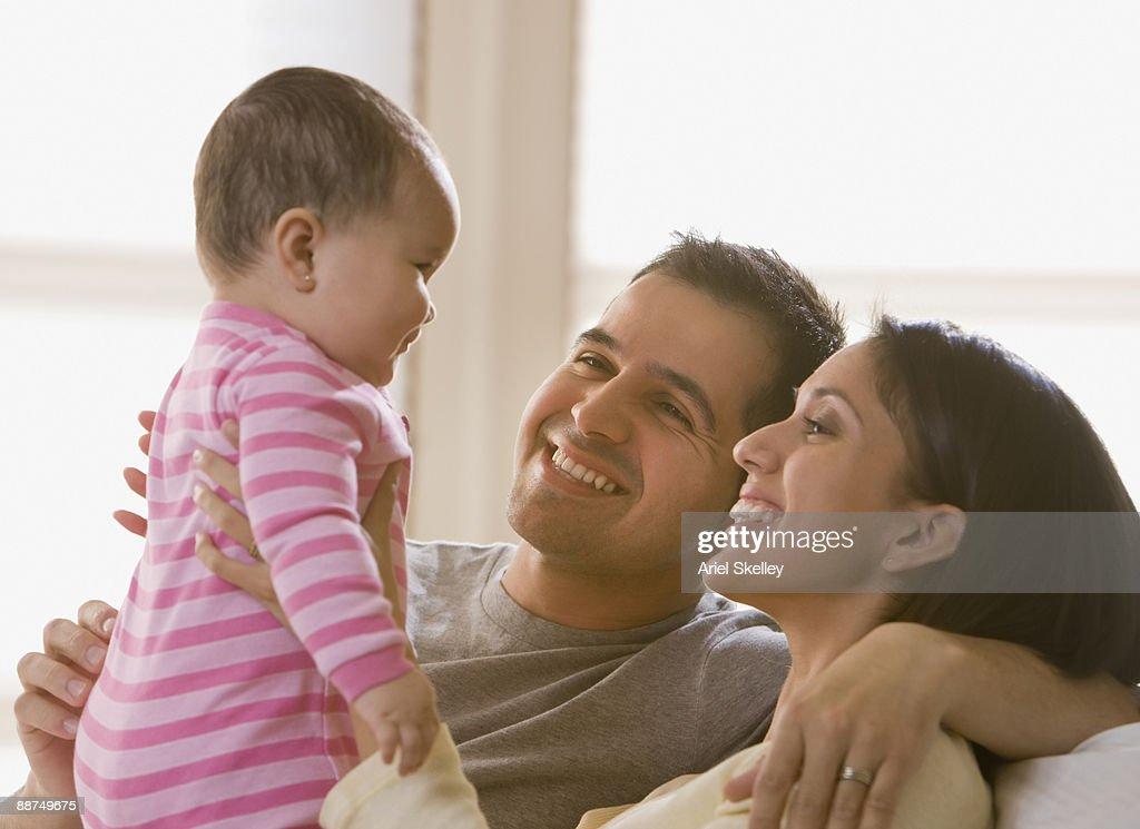 Hispanic couple admiring baby girl : Stock Photo