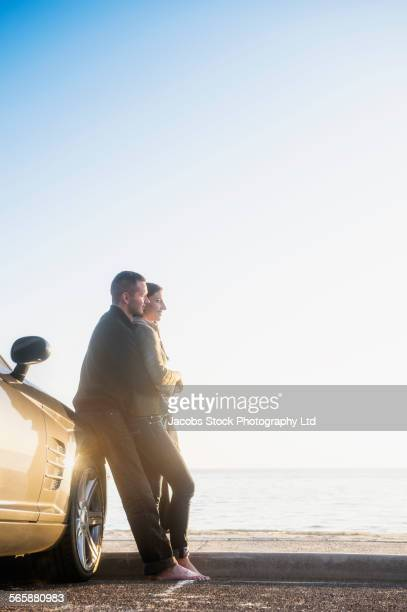 Hispanic couple admiring beach view near car in parking lot
