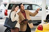 Hispanic couple at car dealership