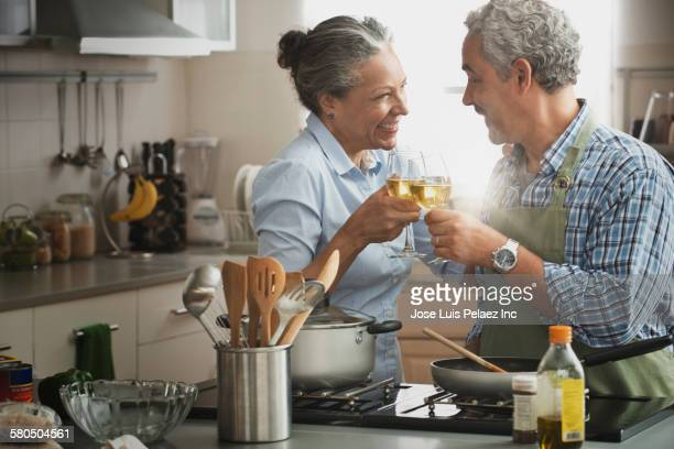 Hispanic couple cooking and drinking wine in kitchen