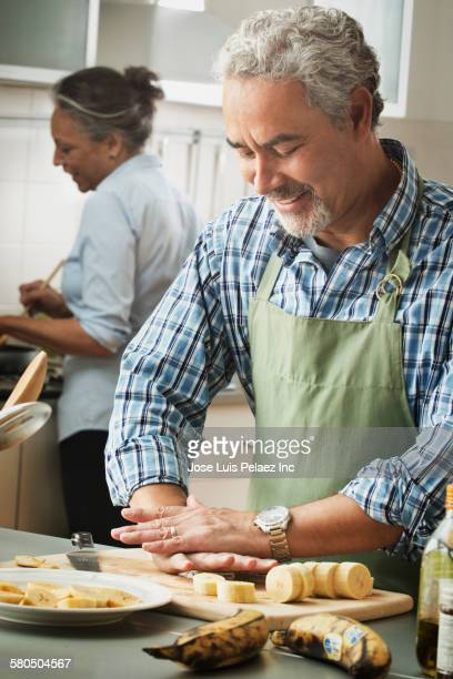 Hispanic couple cooking in kitchen
