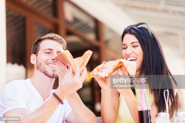 Hispanic couple eating pizza at cafe