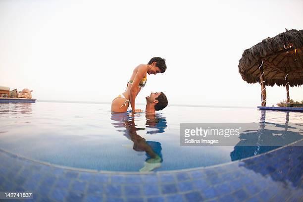 Hispanic couple enjoying swimming pool