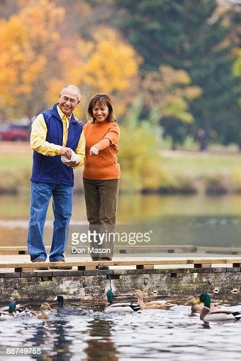 Hispanic couple feeding ducks in pond : Stock Photo
