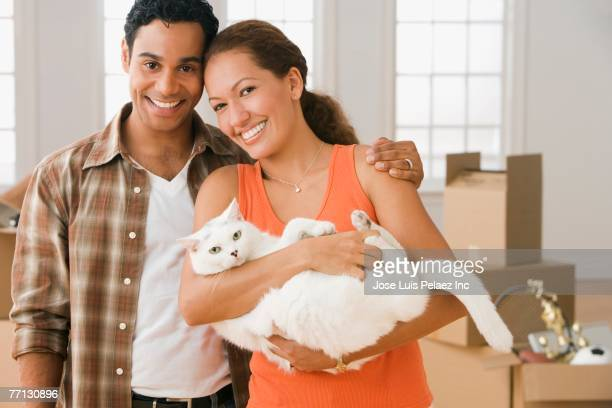 Hispanic couple holding cat in front of moving boxes
