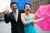 Hispanic couple holding umbrellas in a windy day and laughing