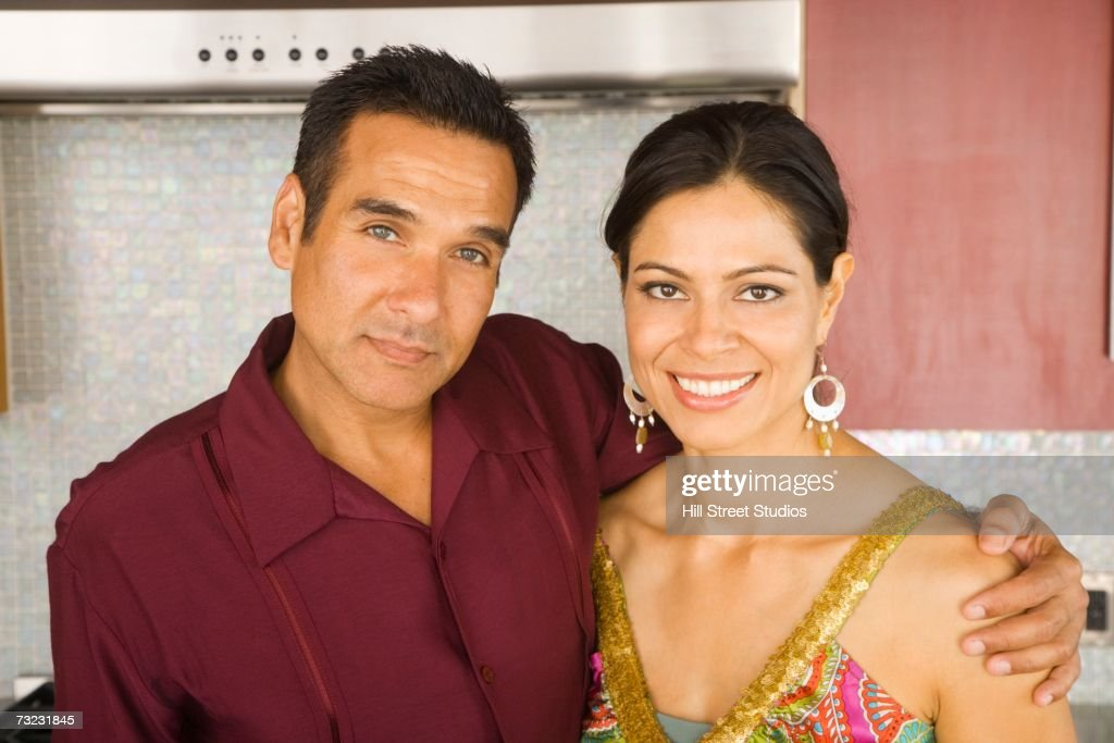 Hispanic couple hugging and smiling in kitchen : Stock Photo