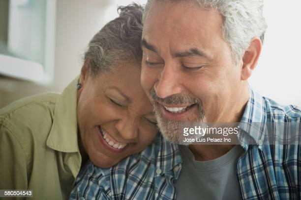 Hispanic couple hugging in kitchen