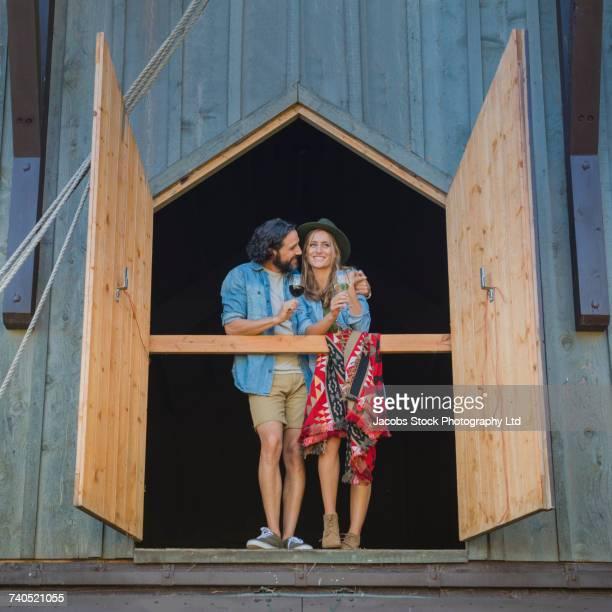 Hispanic couple hugging near open barn doors drinking wine