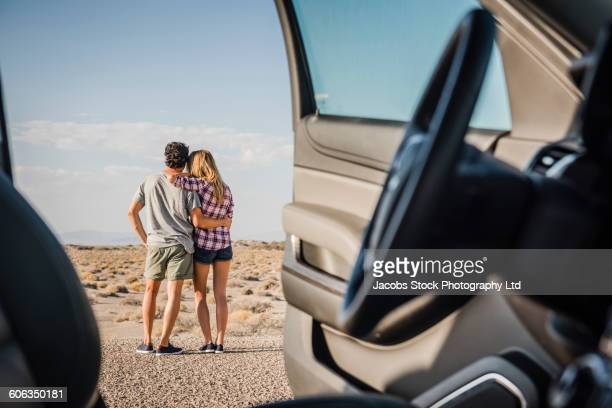 Hispanic couple hugging on remote road