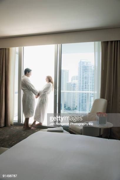 Hispanic couple in bathrobes holding hands by window