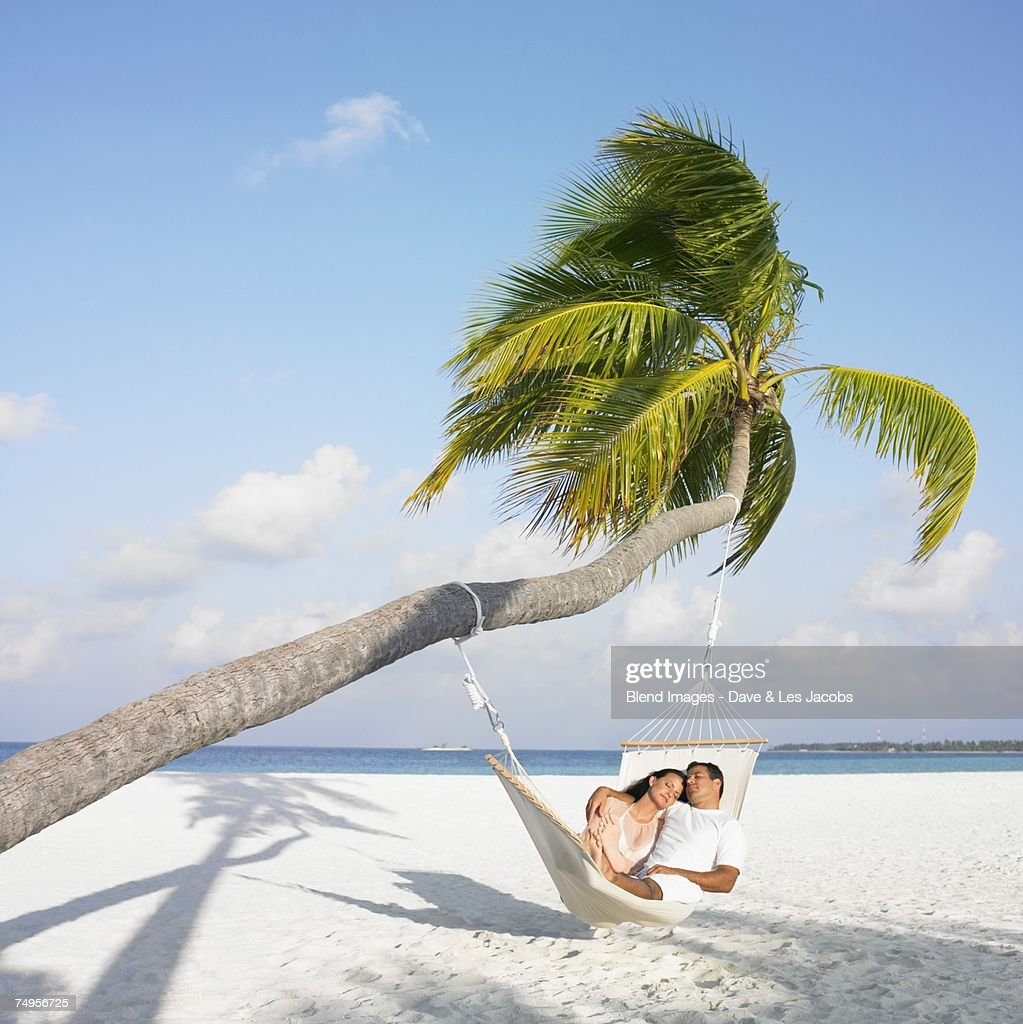 Hispanic couple in hammock at beach