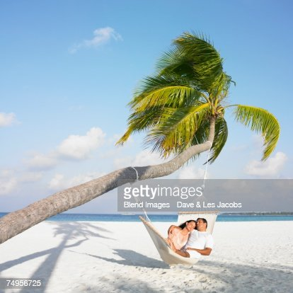 Hispanic couple in hammock at beach : Stock Photo