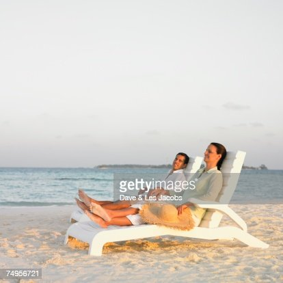 Hispanic couple in lounge chairs at beach : Stock Photo
