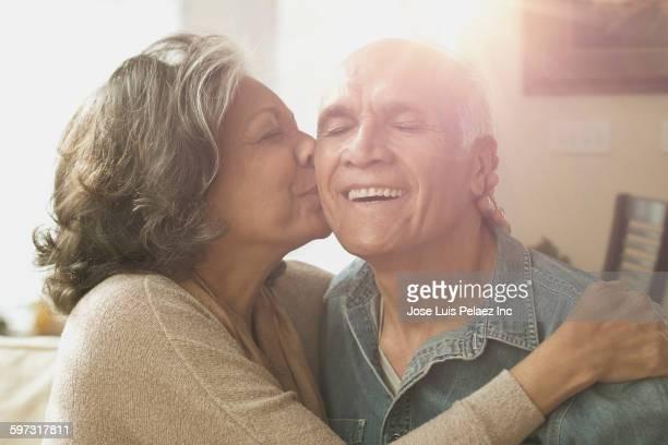 Hispanic couple kissing in living room