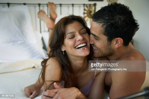 Hispanic couple laughing on bed