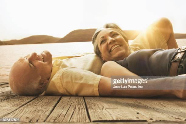 Hispanic couple laying on wooden dock