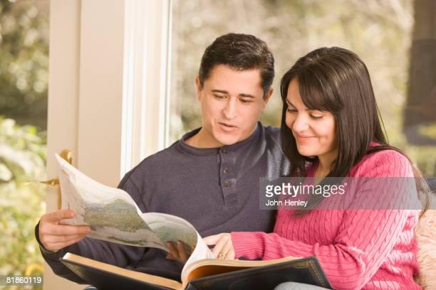 Hispanic couple looking at atlas
