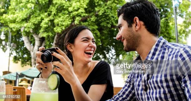 Hispanic couple looking at digital camera in outdoor restaurant