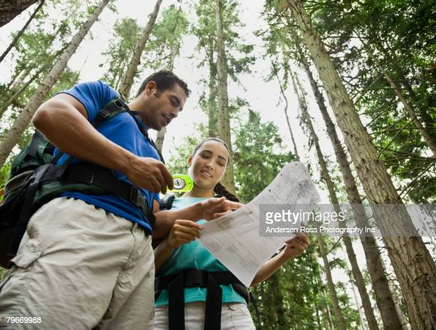 Hispanic couple looking at map in woods