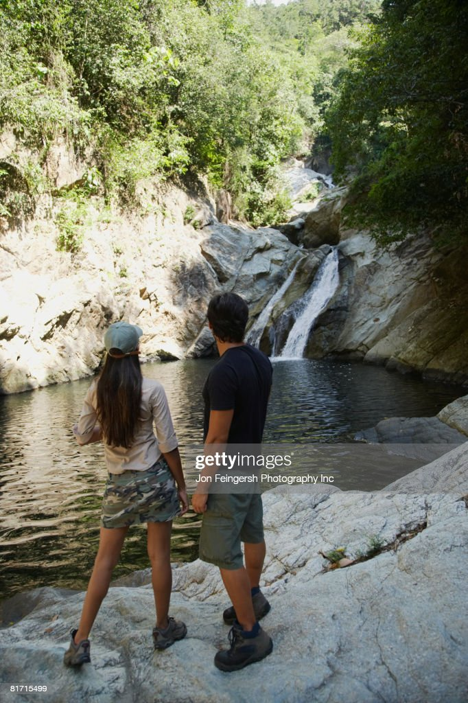 Hispanic couple looking at waterfall : Stock Photo
