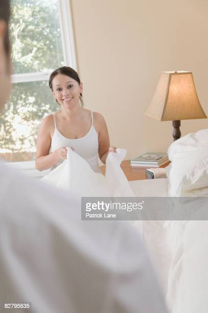 Hispanic couple making bed