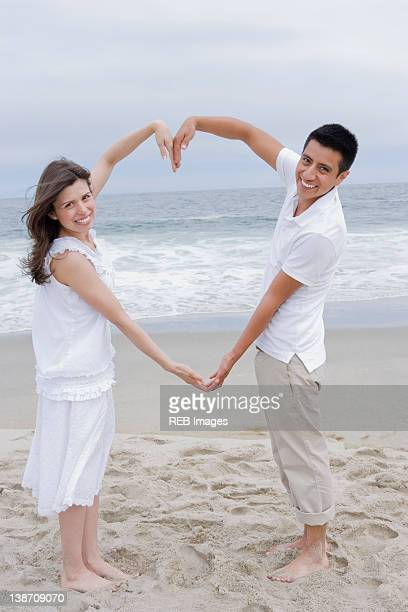 Hispanic couple making heart shape with arms on beach