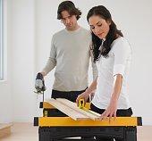 Hispanic couple measuring wood