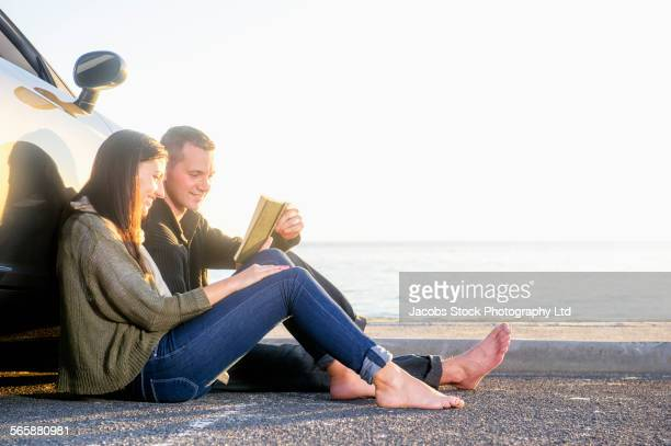Hispanic couple reading book near car in beach parking lot