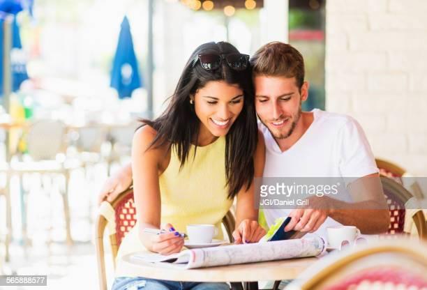 Hispanic couple reading map at cafe