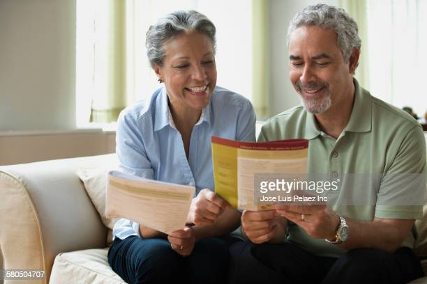 Hispanic couple reading pamphlet on sofa