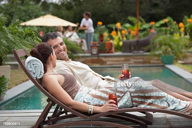 Hispanic couple reclining on lounge chairs near swimming pool