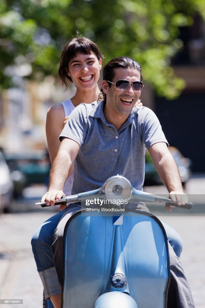 Hispanic couple riding scooter : Stock Photo