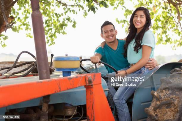 Hispanic couple riding tractor on ranch