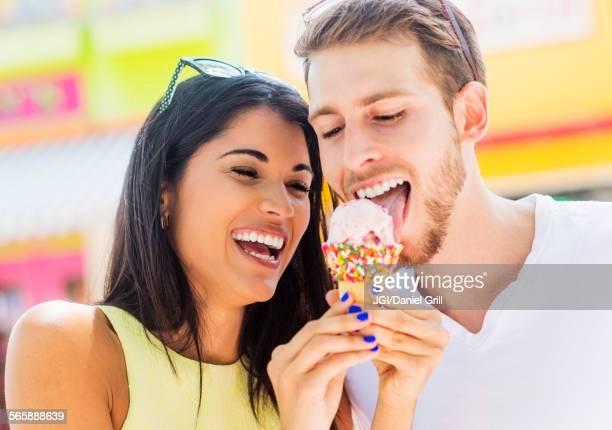 Hispanic couple sharing ice cream cone outdoors