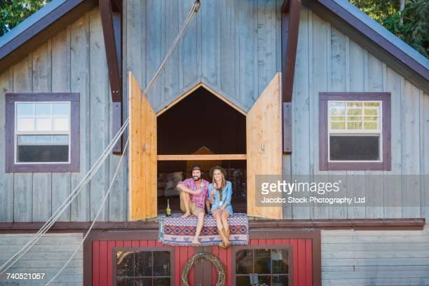 Hispanic couple sitting on blanket near open barn doors drinking wine