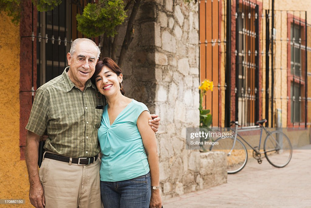 Hispanic couple smiling on city street : Stock Photo