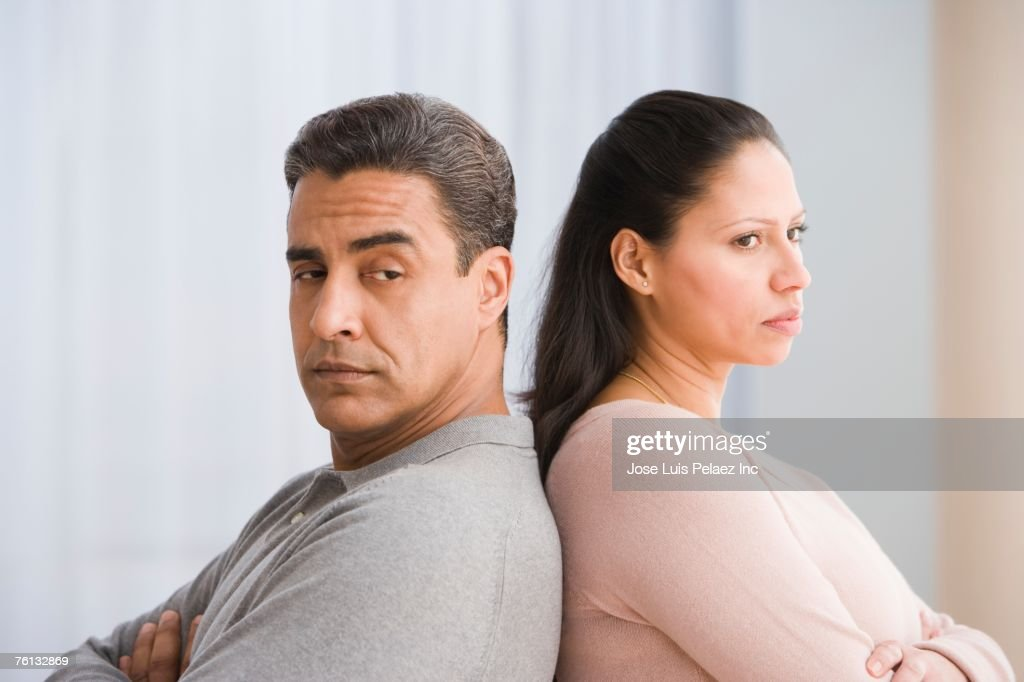 Hispanic couple standing back to back